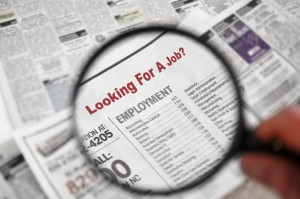 Looking for a Job! Magnifying glass over Jobs section of newspaper classifieds