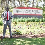 Sterlin Sanders standing next the Valdosta State University sign
